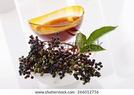Elder, elderberries, glass bowl with elderberry juice - stock photo