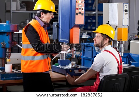 Elder female superior is instructing young male worker - stock photo
