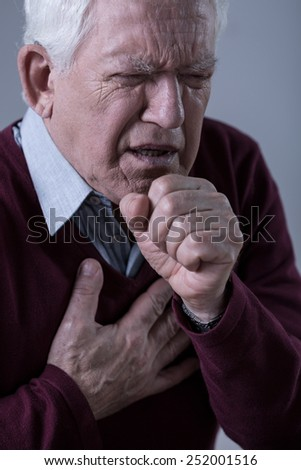 Elder man having pain in chest and coughing - stock photo