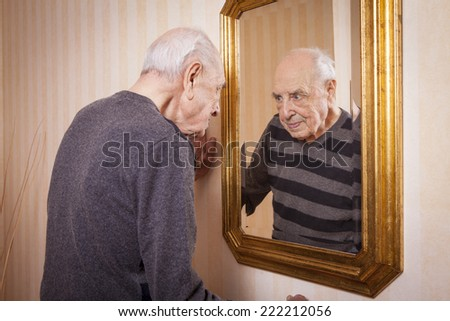 elder man looking at himself at the mirror