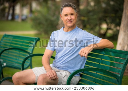 Elder man sitting at a bench in the park - stock photo