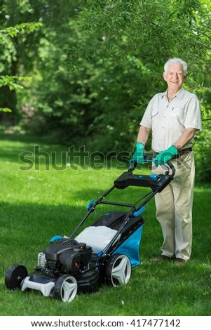 Elder man using the lawnmower in his green garden