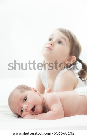 elder sister and the younger newborn child on a white background
