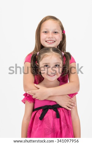 Elder sister hugging her younger sister girl both with pink dress - stock photo