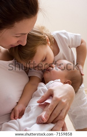 Elder sister kissing baby. Happy young mother holding baby