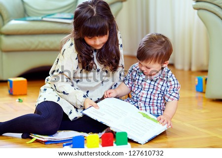elder sister playing with brother at home - stock photo