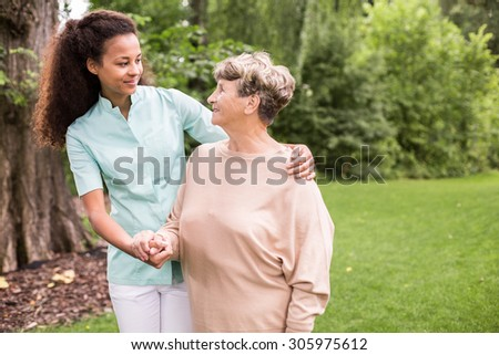 Elder woman and caregiver walking in the park - stock photo