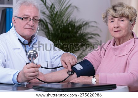 Elder woman controlling blood pressure during visit at cardiologist - stock photo