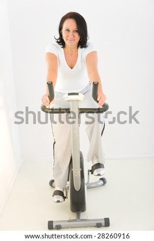 Elder woman exercising on bike. She's smiling and looking at camera. Front view. - stock photo