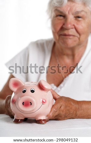 Elder woman holding and hugging funny pink piggybank. Budgeting expenses, making savings, effective investment concept. Future needs deposit. Focus on pig. Retirement and retiree financial problems - stock photo