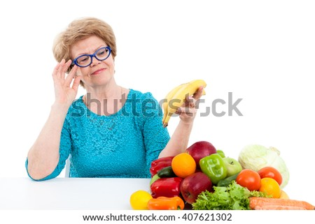 Elder woman looking at ripe bananas in hand, sitting with fresh fruit and vegetables on table, isolated on white background - stock photo