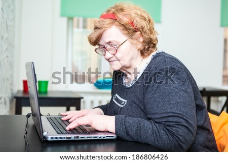 Elder woman looking close and typing on laptop keyboard - stock photo