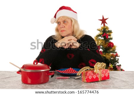 Elder woman of mature age alone with the Christmas dinner - stock photo
