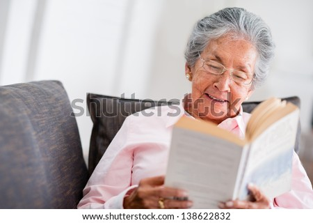 Elder woman reading a book at home and smiling - stock photo