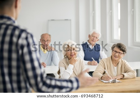 Elder women and men making notes from IT lectures
