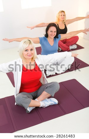 Elder women sitting cross-legged on mat and doing exercices. They're looking at camera. High angle view - stock photo