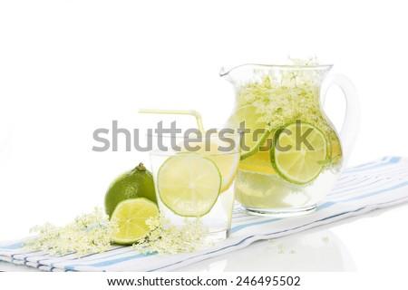 Elderberry lemonade with fresh lemon and lime and elderberry blossom isolated on white background. Fresh summer healthy drink. - stock photo
