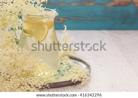 Elderflower juice with lemon in a glass jug. Elderflower lemonade with a slice of lemon and  elderflower on a wooden table. Macro, selective focus, vintage toned image, blank space - stock photo