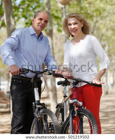 Elderly active married couple with bicycles smiling in public garden