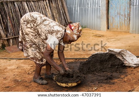 elderly african woman preparing a mixture of cow dung and mud used as a floor covering in traditional huts - stock photo
