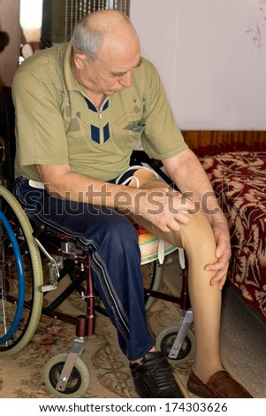 Elderly amputee with a prosthetic leg sitting in a wheelchair at home with his trouser leg rolled up while he fits it to his stump
