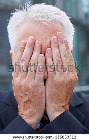 Elderly business man covering his face with both hands