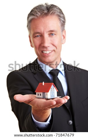 Elderly business man holding a small miniature house on his palm - stock photo