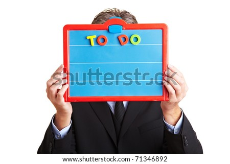 Elderly business man holding a To Do List on a magnetic board - stock photo