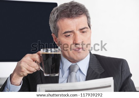 Elderly business man reading a newspaper while drinking a cup of coffee - stock photo