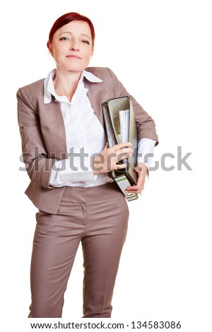 Elderly business woman with red hair carrying files - stock photo