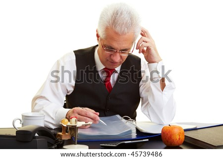 Elderly businessman reading files at his desk