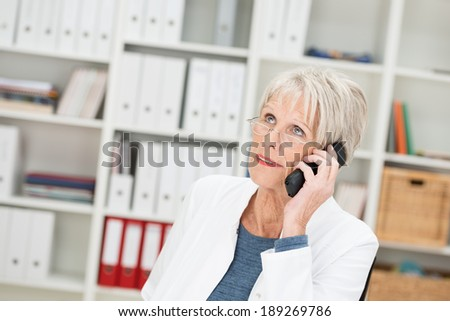 Elderly businesswoman listening to a call on her mobile looking up into the air with a thoughtful expression - stock photo