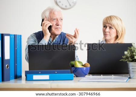 Elderly busy man transacting business cases on the phone - stock photo