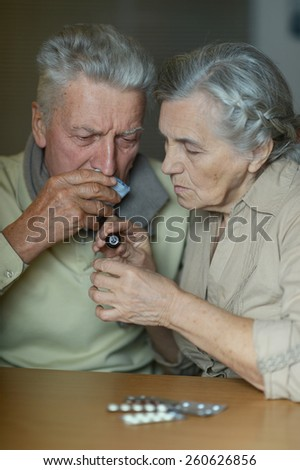 Elderly caucasian couple ill with influenza at home - stock photo