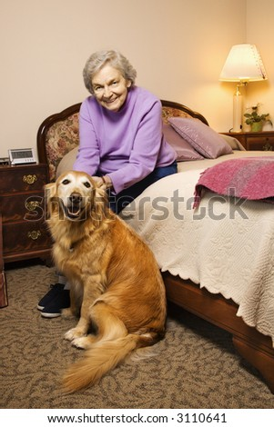 Elderly Caucasian woman and dog in her bedroom at retirement community center. - stock photo