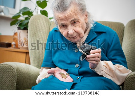 elderly caucasian woman counting coins in her hands - stock photo
