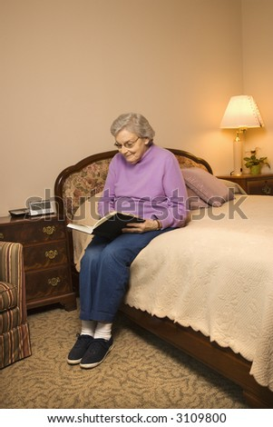 Elderly Caucasian woman in  bedroom at retirement community center reading a book. - stock photo