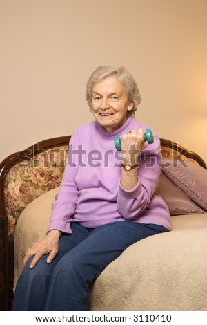 Elderly Caucasian  woman in her bedroom at retirement community center lifting weights to strengthen arms. - stock photo