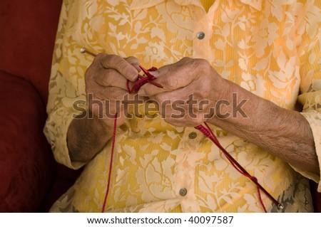 elderly caucasian woman knitting with burgundy wool yarn - stock photo