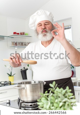 Elderly chef in kitchen preparing food - stock photo