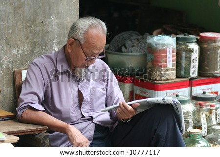 Elderly chinese man reading newspaper in the street in front of his shop