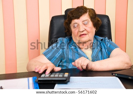 Elderly corporate woman working in her office and using calculator