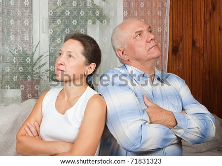 Elderly couple after quarrel on sofa at home - stock photo
