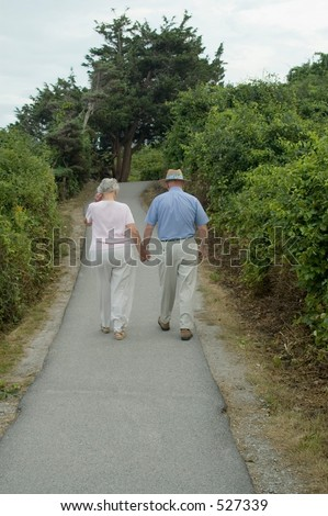 Elderly couple are walking away on the walk road.
