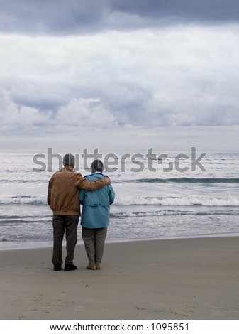 Elderly couple by the ocean - stock photo