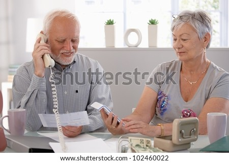 Elderly couple checking bills at home, discussing finances. - stock photo