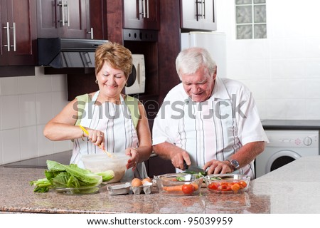elderly couple cooking in home kitchen