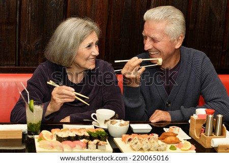 Elderly couple eating sushi in a cafe - stock photo