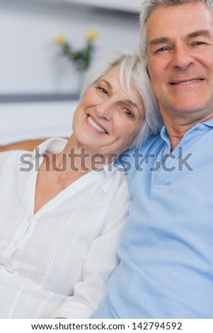 Elderly couple embracing in the kitchen - stock photo