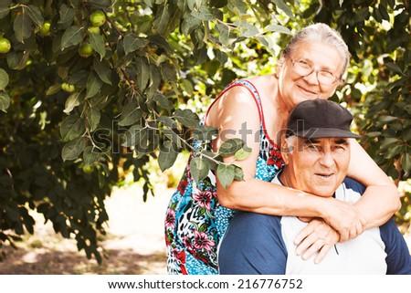 Elderly couple. Happy family. Pensioners. Cherry garden - stock photo